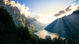 Фотографии Горы Озеро Швейцария Альпы Лучи света Klontalersee Природа