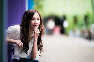 Фото Азиатки Размытый фон Шатенка Взгляд Рука молодая женщина