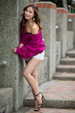 Фото Азиатки Шатенка Поза Ноги Шорт Улыбка Размытый фон молодая женщина