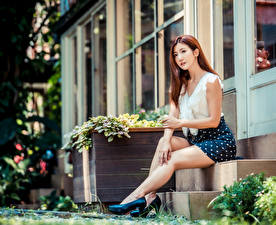 Картинки Азиатка Шатенки Сидящие Туфель Ноги Юбке Блузка Размытый фон Лестницы