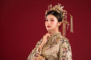 Обои Азиаты Украшения Макияж Платье Смотрят Красном фоне молодые женщины