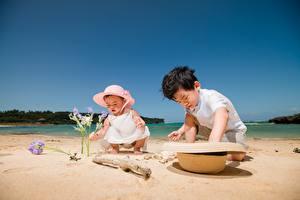 Картинки Лето Азиатки Пляж Две Играет Шляпы Песок Мальчишки Девочка ребёнок