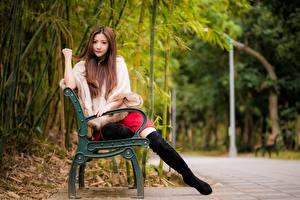 Картинки Азиаты Размытый фон Скамейка Шатенки Сидит Ноги Сапогов молодая женщина