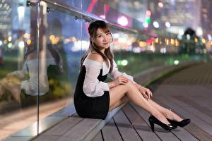 Картинки Азиаты Шатенка Размытый фон Улыбается Сидя Руки Ноги Туфли молодая женщина