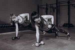 Фото Фитнес Черно белое Две Гантелями Тренируется Рука Планка упражнение молодые женщины
