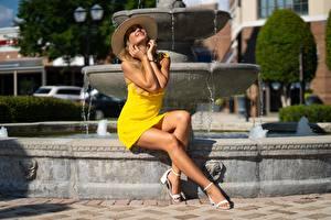 Картинка Фонтаны Платья Желтая Шляпы Рука Улыбается Красивая Ног Сидящие Позирует Девушка