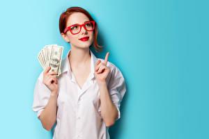 Фото Деньги Доллары Цветной фон Рыжие Очков Красными губами Рука Взгляд Рубашке молодая женщина