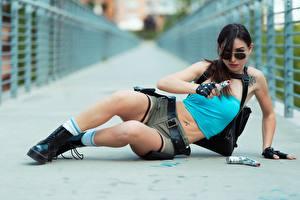 Картинки Пистолет Брюнетка Лежачие Руки Очках Перчатки Шорты Ног Ботинки Косплей Лара Крофт девушка
