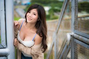 Картинки Азиатка Размытый фон Шатенки Взгляд Улыбка молодая женщина
