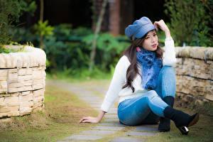 Картинка Азиатка Боке Шатенки Свитер Рука Ноги Сидя Джинсы Бейсболка молодые женщины