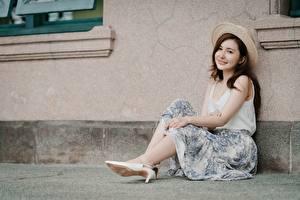 Картинка Азиатка Шатенки Шляпа Рука Сидя Ноги молодая женщина