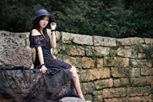 Картинки Азиатка Брюнетки Размытый фон Платье Шляпа Руки Сидит Девушки