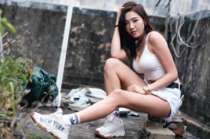 Фото Азиатка Сидящие Кроссовки Ног Шорт Майке Взгляд молодая женщина