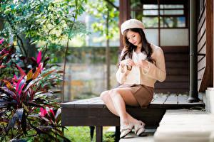 Картинки Азиатка Сидящие Юбке Берет Ноги Размытый фон молодая женщина