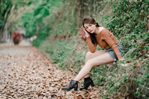 Картинки Осенние Азиатка Листья Шатенка Сидящие Боке Ног молодые женщины