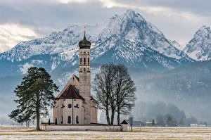 Фото Германия Гора Церковь Бавария Альпы Дерево Снег St. Coloman Природа