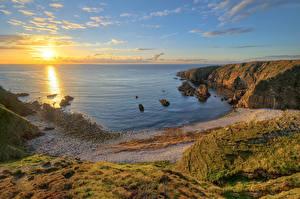 Фотографии Ирландия Побережье Рассвет и закат Океан Скала Солнца Горизонт Donegal Природа