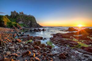 Картинка Великобритания Берег Камень Рассвет и закат Замок Руины Скала Солнца Northern Ireland, Dunluce Castle Природа