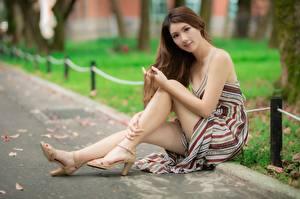 Фотографии Азиатка Размытый фон Шатенка Платья Сидя Рука Ноги Туфлях молодые женщины
