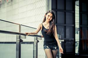 Обои Азиатка Боке Брюнетки Смотрят Улыбка Руки Шорт молодая женщина