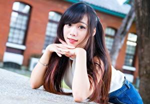 Обои для рабочего стола Азиатка Размытый фон Руки Лежат Смотрит Шатенки молодые женщины