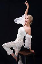 Картинки Азиатка Стул Поза Блондинка Рука Черный фон молодые женщины
