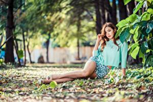Фотография Азиатки Сидящие Листва Ног Блузка Смотрит Боке девушка