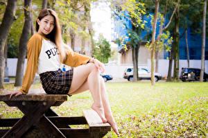 Обои для рабочего стола Азиатки Сидит Столы Ног Юбки Улыбка Смотрят молодая женщина