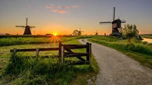 Обои для рабочего стола Голландия Рассвет и закат Дороги Мельница Трава Забор Kinderdijk Природа