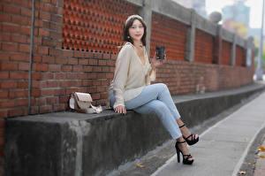 Фото Азиаты Сумка Сидя Джинсов Стена Кирпичный Взгляд молодые женщины