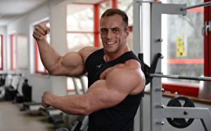 Картинка Бодибилдинг Мужчины Рука Мускулы Улыбка Смотрит Спорт