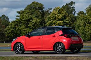 Картинки Тойота Красная Металлик Сбоку Yaris Hybrid UK-spec, 2020 авто