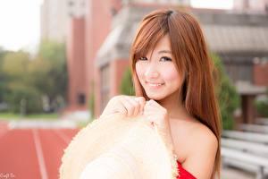 Фотография Азиатки Размытый фон Рыжих Смотрит Улыбка Руки Шляпа девушка