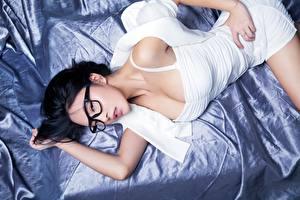 Фотографии Азиаты Брюнетка Лежит Очки Взгляд Руки молодые женщины