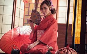 Фотографии Азиаты Шатенки Кимоно Смотрит Сидя Рука Веер Японский Japanese молодые женщины