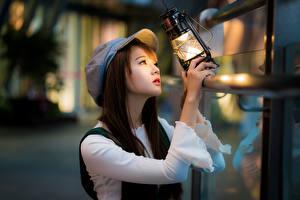Картинки Азиаты Керосиновая лампа Кепка Размытый фон Девушки