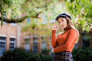 Картинка Азиатка Позирует Ветки Свитере Кепка Смотрит молодые женщины