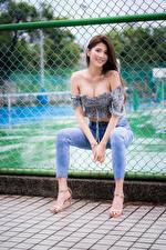 Картинки Азиаты Сидя Забор Джинсы Блузка Улыбается Взгляд молодые женщины