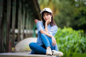 Обои Азиатки Сидящие Джинсов Рубашке Бейсболка Смотрит Боке девушка