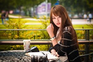Фото Азиатка Наручные часы Шатенки Смотрят Руки Сидит Боке молодая женщина