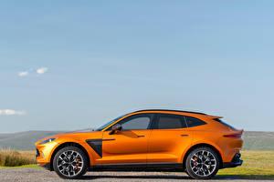 Фотографии Aston Martin Оранжевая Металлик Сбоку CUV DBX, North America, 2020 Автомобили