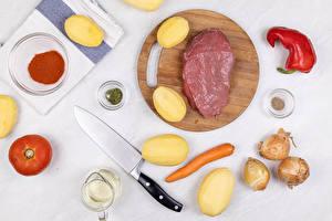 Фотография Мясные продукты Картофель Лук репчатый Морковь Перец Помидоры Ножик Специи Разделочной доске Продукты питания