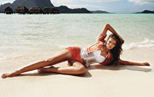 Фотографии Море Пляж Лежачие Позирует Шорт Шатенки Мокрые Ноги Девушки