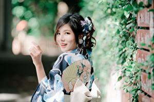 Фото Азиаты Размытый фон Рука Брюнетки Смотрит Улыбается девушка