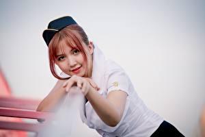 Фотографии Азиаты Размытый фон Стюардесса Смотрят Улыбка Руки Рыжие девушка