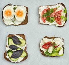 Картинка Бутерброды Хлеб Томаты Огурцы Овощи Сером фоне Масла Яйца Еда