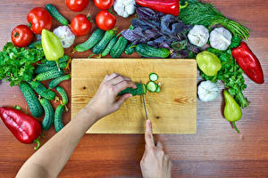 Фото Овощи Помидоры Перец овощной Огурцы Чеснок Доски Разделочная доска Руки Еда