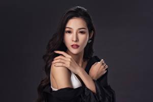 Фотография Азиаты Брюнетки Руки Смотрит Серый фон молодые женщины