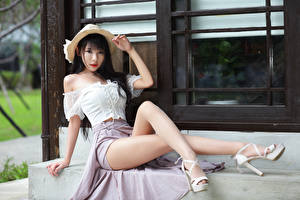 Картинка Азиатки Брюнеток Сидя Шляпа Ног Смотрят Красивая молодая женщина