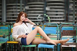 Картинки Азиатки Сидит Ног Шорт Блузка Взгляд Шатенки молодые женщины